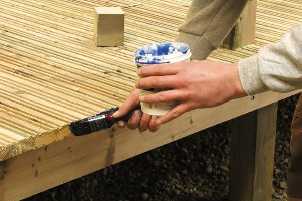 End grain preservative being applied to cut timber