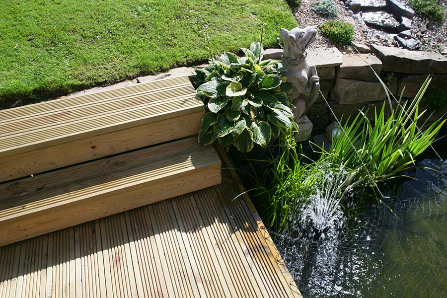 Close-up of grooved timber deck with pond