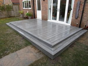 Raised grey Trex deck attached to patio double doors