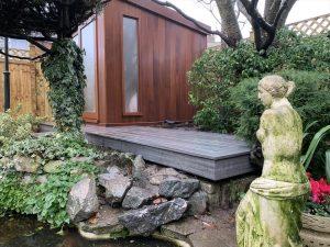 Small grey Trex outside garden summer house