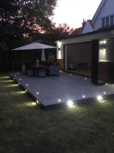 Decking with solar lights and lounge area at night