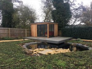 Decking overhanging a pond with an outhouse