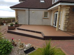 Brown Trex decking area with planters next to house