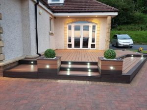 Raised deck area with spotlights and planters