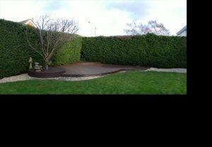 Curved brown deck in corner of garden