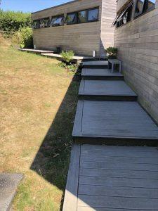 Mmulti-level Trex decking in grey in a sloping garden