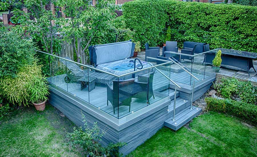 Raised grey decking area on garden. Steps lead to outdoor furniture area and set in jacuzzi.