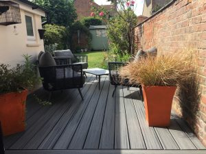 Grey Trex deck with outdoor lounge chairs and coffee table surrounded by potted plants