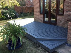 Grey trex deck on the rear of a brick house with a potted plant next to it