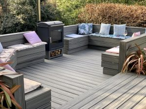 Trex Island Mist deck with built-in seating area and log burner