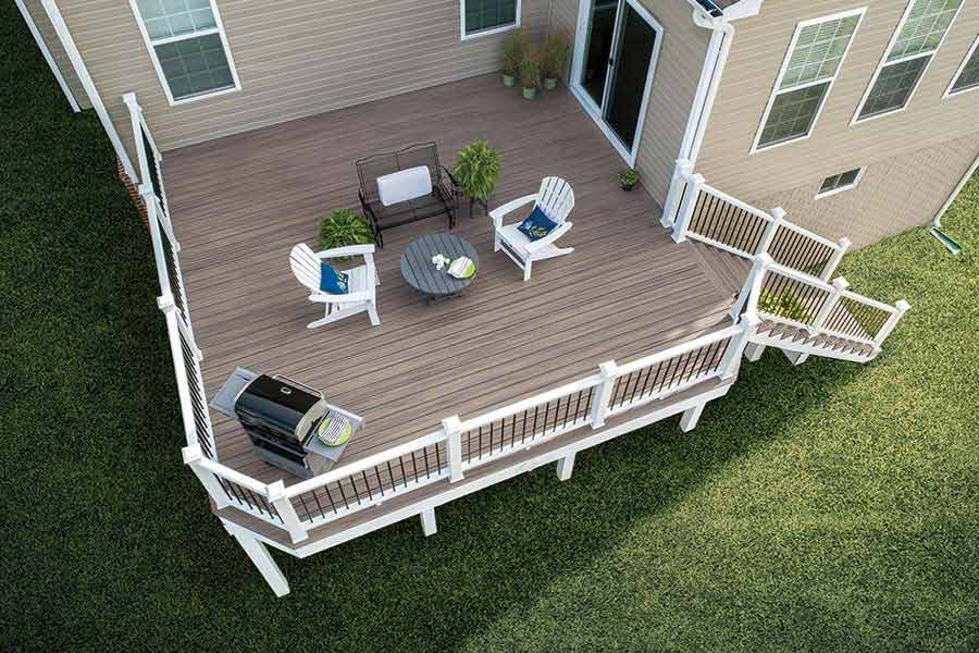 Birdseye view of raised brown decking with furniture. White trim fencing.