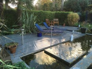 View over a square pond of brown decking with sun loungers on grey decking. Surrounded by trees and hedges.