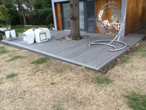 Grey decking on a grass area leading to an out house.
