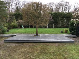 Grey decking with a tree in the middle on a grass area.