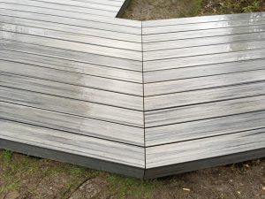 Grey decking on a dirt area.