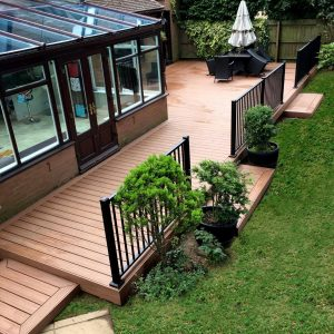 Birdseye view of grass back garden with raised brown decking area with black railing.