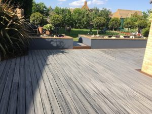 Grey decking leading to a grass area of a back garden.