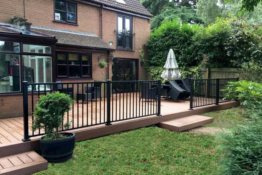 Grassy garden area led with a path to raised brown decking area and black railing at the back of a house.