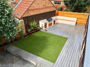 Aerial view of a garden containing a grey trex deck, BBQ station and artificial grass.