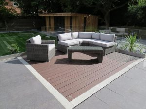 Brown Trex Deck with lighting and an outdoor corner sofa sat on top of it.