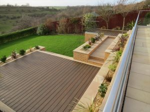 Aerial view of a brown Trex deck surrounding by sandstone pavers and yellow bricks.