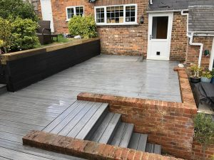 Grey deck in between a brick wall and a black sleeper retaining wall.
