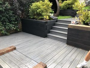 Grey deck positioned infront of a black sleeper retaining wall