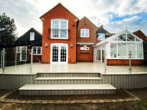 Trex decking attached to house with glass railings and steps to the garden
