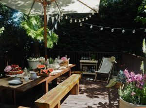 Trex deck underneath a dining table with a sleeper bench and parasol.