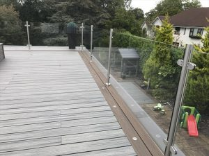 Trex decking balcony with different colour board edging and glass railings
