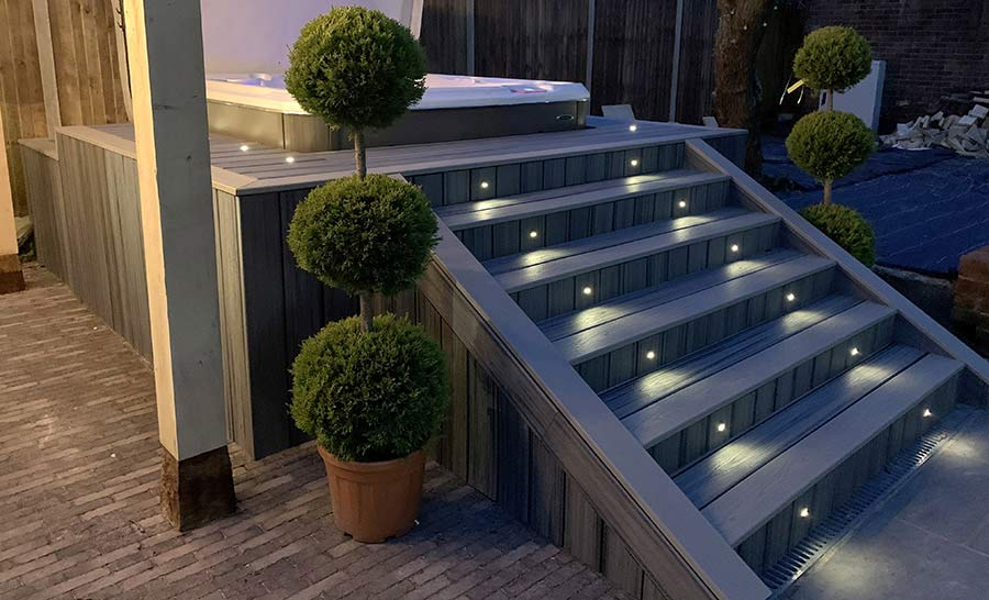 Trex deck surrounding a hot tub with Trex lighting on steps.