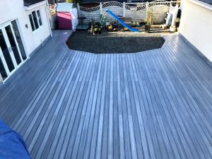 Grey Trex deck in a garden surrounding a children's play area.