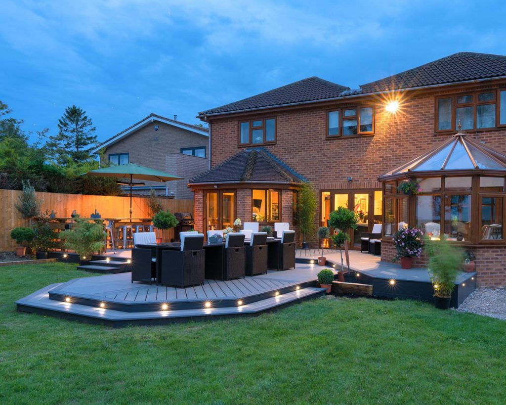 Trex deck behind a house with Trex lighting and a dining table on top