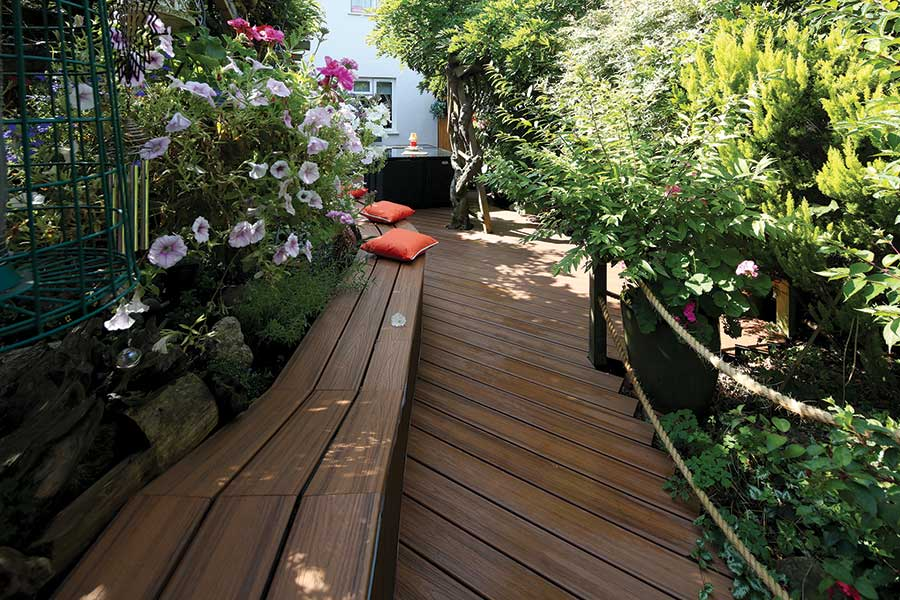 Trex deck path with bench through a green bushy garden with rope railings