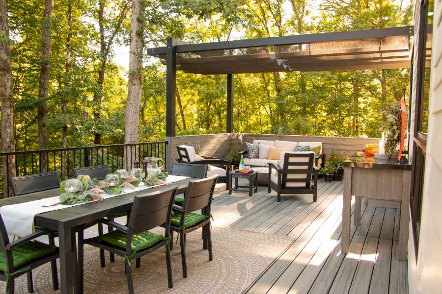 Trex deck at the rear of a brick house with Trex lighting and a dining table a top.