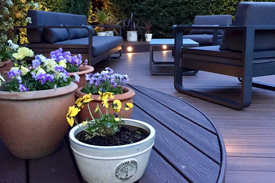 Curved Trex deck with a modern sofa and plant pots