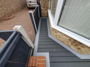 Small grey Trex deck next to a gate