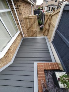 Small grey Trex deck next to a timber gate